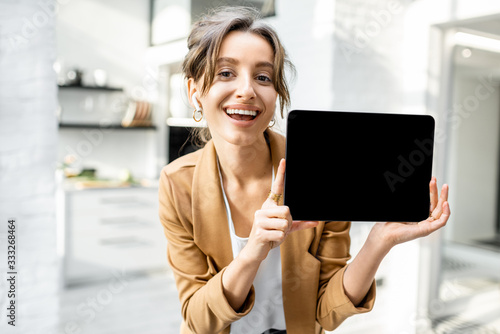 Obraz Well-dressed cheerful business woman with a digital tablet indoors, showing tablet with a black screen to copy paste - fototapety do salonu