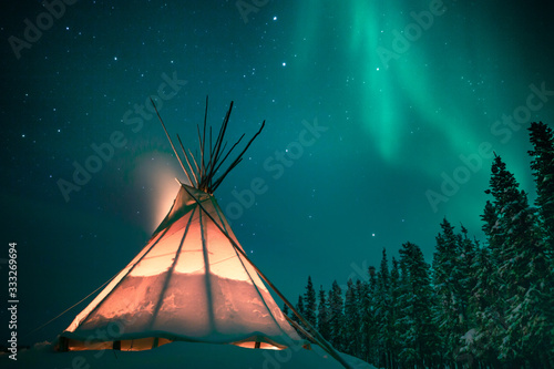 Glowing tipi / teepee in the snowy forest under the northern lights, Yellowknife Wallpaper Mural