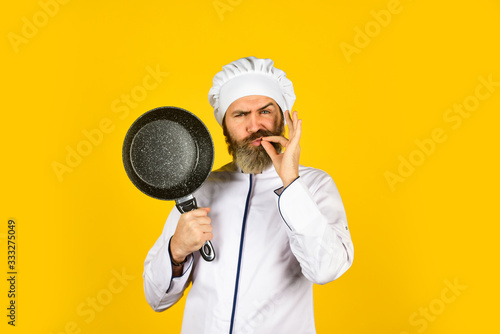 Fototapeta Professional kitchenware. Frying meal. Healthy food. Bearded chef preparing breakfast. Nonstick pan for frying. Enameled cooking vessels. Man hold pan. Nonstick cookware. Frying without oil obraz