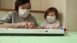 an adult woman,with a little girl, learning to play the piano, during a home quarantine, due to the covid-19 pandemic