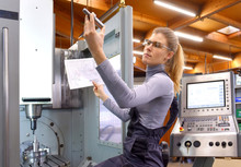 A Young Woman Works As A Computerized  Numerical Control Technician. She Is Seen At Her Workplace Wearing A Blue Overall.