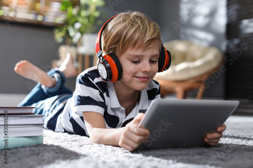 Fotografia Cute little boy with headphones and tablet listening to audiobook at home