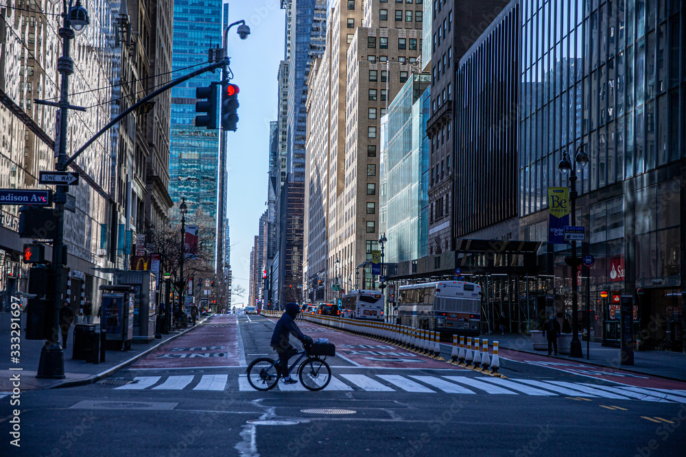 Fototapeta A person rides his bike through the near empty streets near Grand Central due to health concerns to stop the spread of Coronavirus in New York City on Tuesday, March 24, 2020. (Photo: Gordon Donovan).