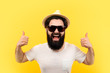 cheerful bearded guy in sunglasses and a panama hat, man shows like on yellow background, concept of a cool vacation