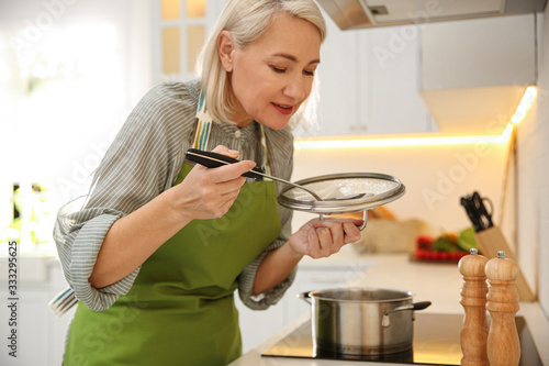 Fotografia Mature woman cooking on stove in kitchen