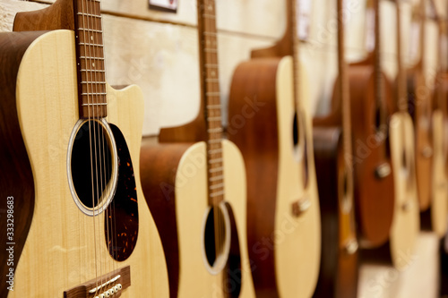 A view of several acoustic guitars hanging on the wall of a music store Tapéta, Fotótapéta