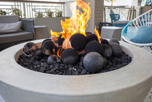 A Closeup View Of A Modern Fire Pit With Decorative Fire Stones.