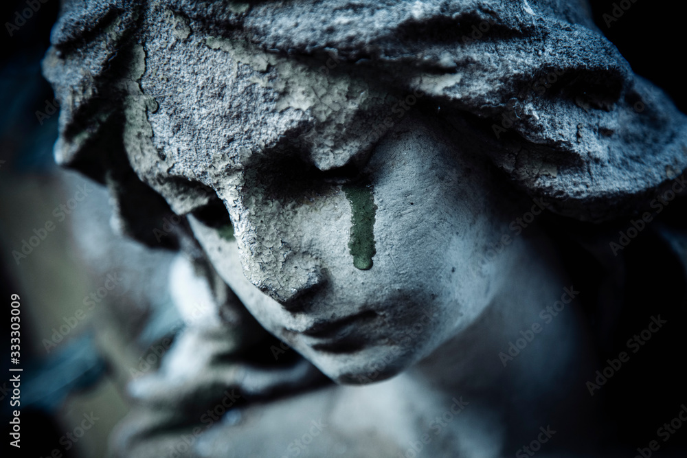 Fototapeta Ancient stone statue of crying sad angel with tears in face as symbol of death and end of human life.