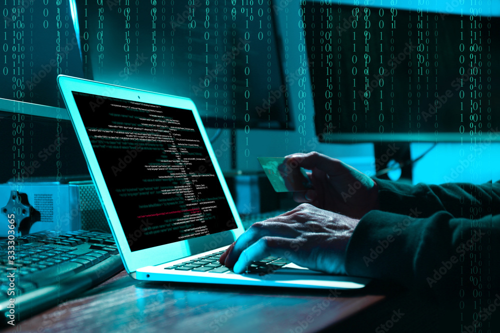 Fototapeta Cyber criminal with credit card hacking system at table, digital binary code on background