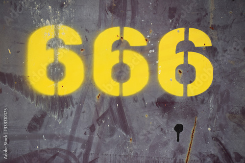 фотография Yellow spray painted number 666 on a wall