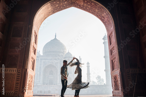 Travel couple dancing at the Taj Mahal