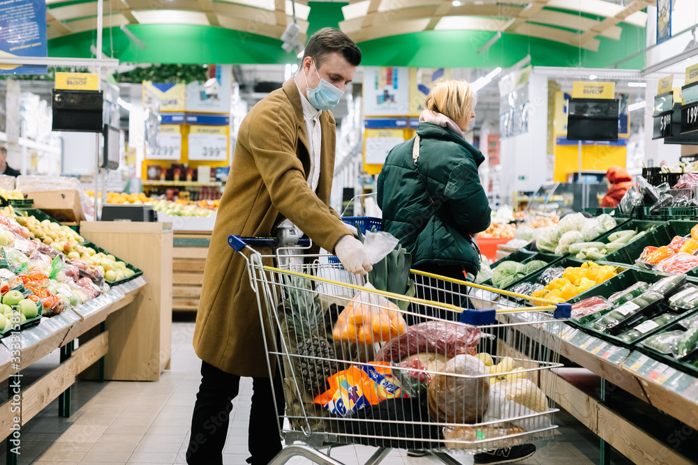 Fototapeta a man in a medical mask buys food at a grocery store. Coronavirus, virus, infection, epidemic, pandemic. RUSSIA, RUSSIA-MARCH 19, 2020. OBNINSK