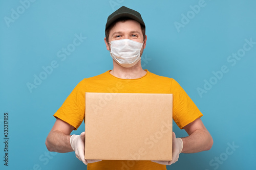 Photo Young delivery man in nedical mask holding and carrying a cardbox on blue wall