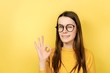 canvas print picture - No problem concept. Closeup portrait young woman in eyeglasses makes okay gesture, has everything under control, all fine gesture, wears spectacles and jumper, poses against yellow background.