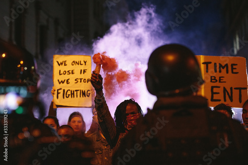 Fototapeta Group of activists protesting with smoke grenades