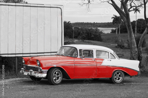 Photo colorkey of classic red and white car on the road in vinales cuba