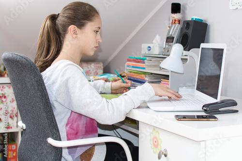 Dziewczynka pisze na laptopie zadanie - fototapety na wymiar