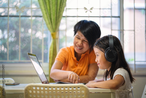 Fényképezés Asian girl and her teacher using laptop for online study during homeschooling at home