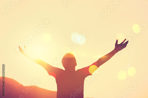 Copy space of man rise hand up on top of mountain and sunset sky abstract background Fototapet