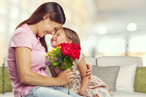Obraz na plátně Happy beautiful mother and daughter hugging with bouquet