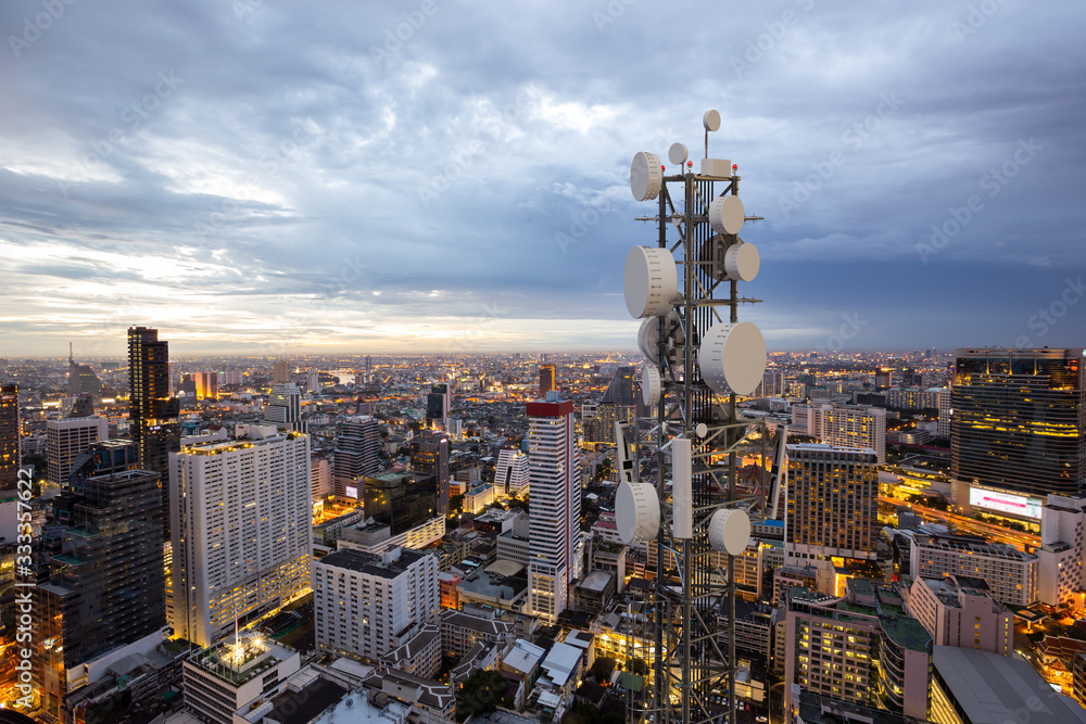 Fototapeta Telecommunication tower with 5G cellular network antenna on night city background
