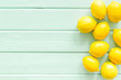Lemons frame - whole fruits - on green wooden table top-down copy space