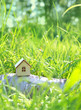 Leinwanddruck Bild - wooden house in green grass. Eco Friendly home. Symbol of family, Mortgage, Real estate concept. copy space