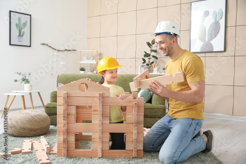 Tableau sur Toile Father and little daughter dressed as builders playing with take-apart house at