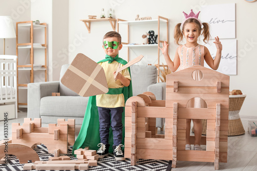 Fotografía Little children in costumes playing with take-apart house at home