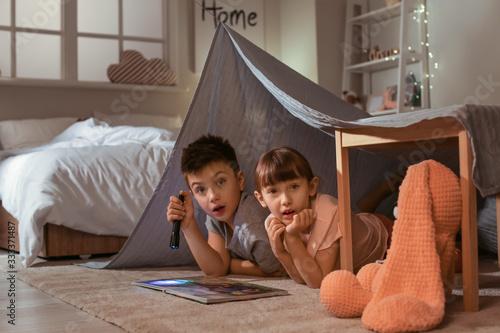 Fotografiet Scared little children reading bedtime story at home