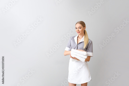 Beautiful young chambermaid with towels on light background