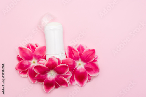 Photo body antiperspirant deodorant with flowers on pink background with a copy space