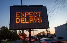 Electrionic Traffic Sign Stating Expect Delays With Blurred Traffic At Sunset