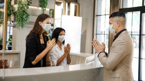 Fotografia hotel guest and receptionist wearing mask to protect from conronavirus covid 19