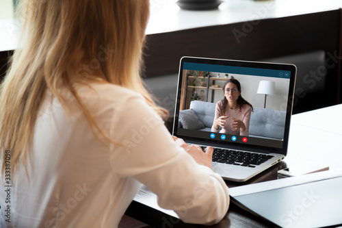 Young girl student woman holding educational video call with teacher on computer, learning foreign language online from home, using videoconference application, chat communicate distantly with friend.