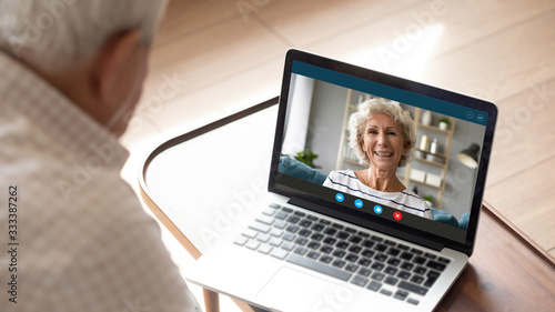 Photo Side shoulder view older senior man looking at laptop monitor, talking speaking chatting with middle aged happy mature woman, communicating with wife online via video call, staying alone at home