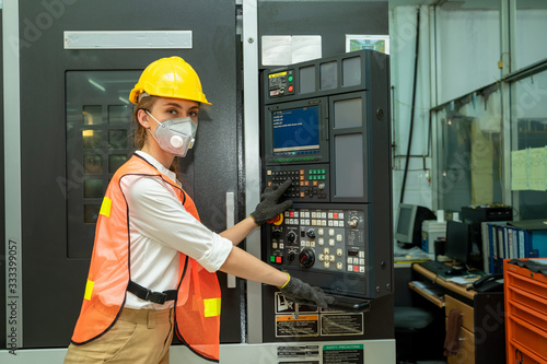 Obraz Female Mechanic wearing  protective mask to Protect Against Covid-19,Female technician worker working and checking machine in a large industrial factory,Coronavirus has turned into a global emergency - fototapety do salonu