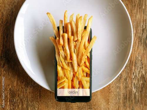 Ordering and delivery of food through the mobile application. Fast food, french fries. © Serge Touch