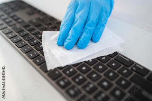 Fototapeta Covid-19 sanitizing office space wiping corona virus cleaning and disinfection of your workspace. Disinfecting wipes to wipe surface of desk, keyboard, mouse at office. Stop the spread of coronavirus. obraz