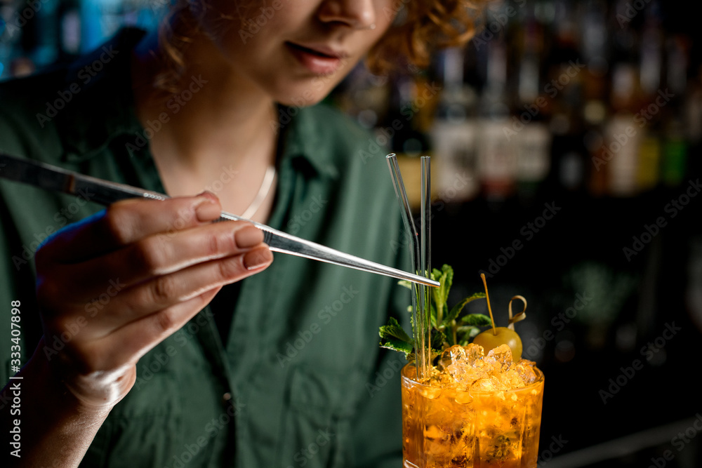 Fototapeta Woman using tweezers accurate decorates cocktail by glass sticks