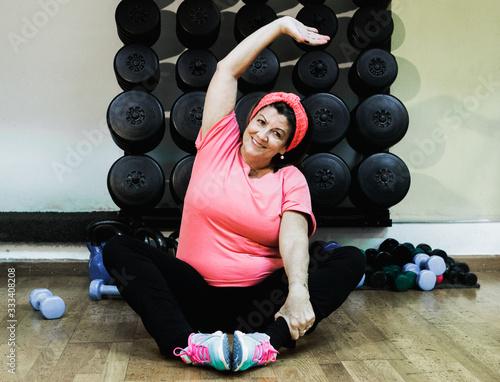 Photo Signora anziana fa esercizio in palestra con i pesi e si diverte