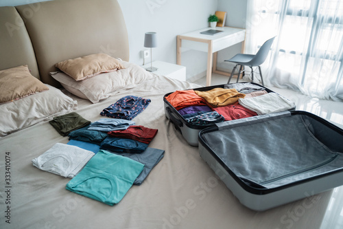 Fototapeta open suitcase with a lot of clothes on the bed in the bedroom