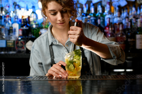 Fototapeta Young woman barman accurate preparing cocktail with slices of citrus fruits obraz