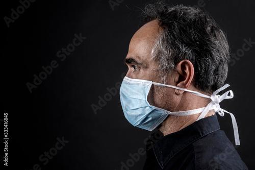 Fotografia, Obraz Profilo di uomo che indossa una mascherina azzurra, isolato su sfondo nero con e