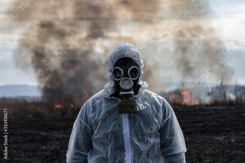 Photo A man in a gas mask in a chemical protective suit shrouded in smoke is walking in a dangerous radioactive zone
