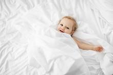 Smiling Baby Lying In White Sh...