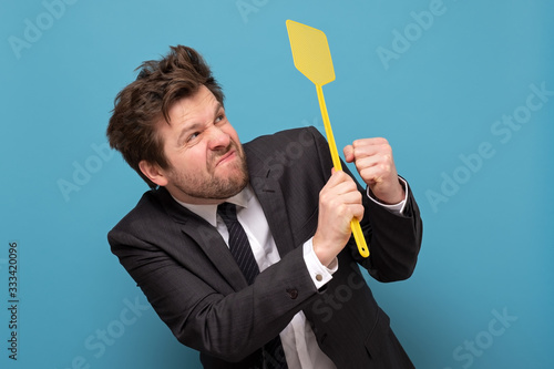 Photo man in suit holding a fly swatter wanting to kill annoying mosquito