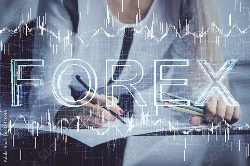 Double exposure of hands making notes with forex chart huds. Stock market concept.