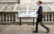 London Civil Servant. A Suited Office Worker Passing A Street Sign For Parliament Street And Whitehall In The Civil Service District Of Westminster.