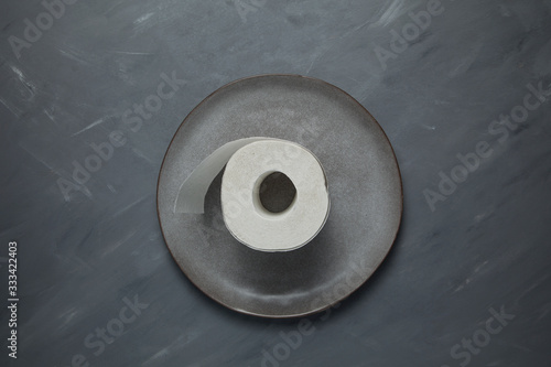 Cuadros en Lienzo Gray plate with a roll of toilet paper on a gray background